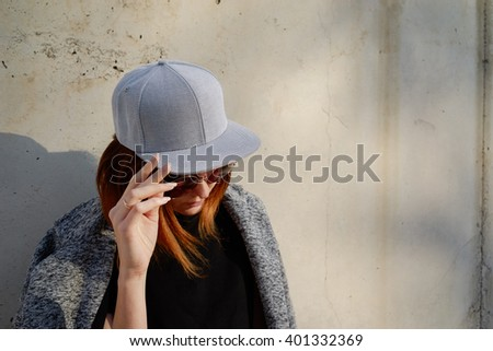 Portrait of a young attractive girl with cap. Female model wearing a gray blank cap and sunglasses looking away. - stock photo