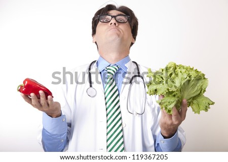 Portrait of a young attractive man doctor holding green salad and red pepper.