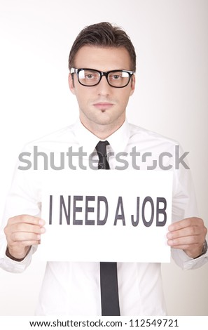 Portrait of a young attractive man holding a sign i need a job.