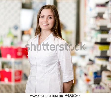 Portrait of a young attractive pharmacist standing in a pharmacy interior looking at the camera - stock photo