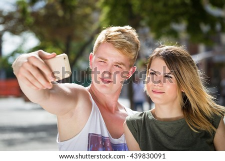 portrait of a young attractive tourist couple using a smartphone to take a selfie picture of themselves on holiday - stock photo