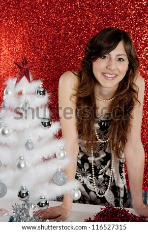 Portrait of a young attractive woman decorating a small christmas tree while standing in front of a red glitter background. - stock photo