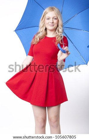 Portrait of a young attractive woman in red dress holding a blue umbrella.