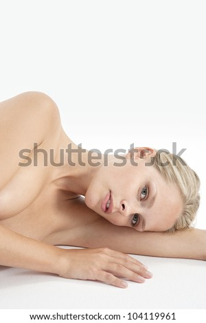 Portrait of a young attractive woman laying naked on a white background. - stock photo