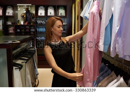 Portrait of a young attractive woman shopper holding stylish shirt for men while standing in brand store, gorgeous caucasian female seller looks at quality garments during work day in fashion boutique - stock photo