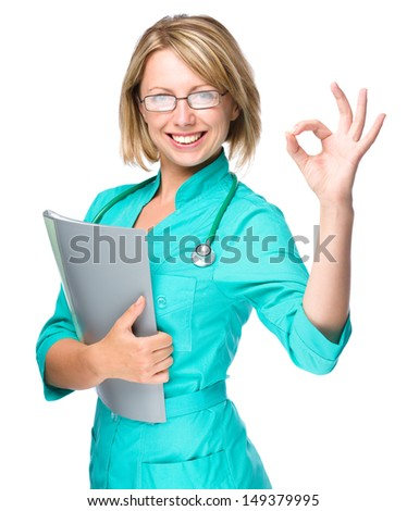Portrait of a young attractive woman wearing doctor uniform showing OK sign, isolated over white - stock photo