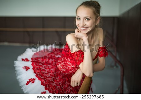 Portrait of a young ballerina with a beautiful smile. The model looks at the camera. Dressed in elegant red tutu. - stock photo