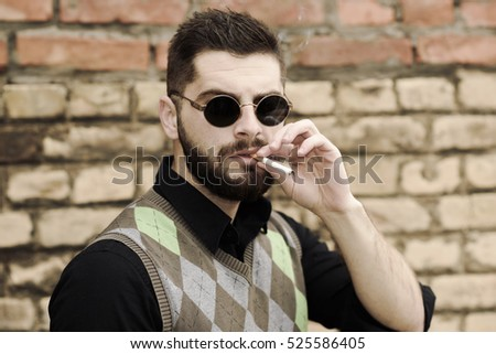 Portrait of a young bearded man who smokes a cigarette