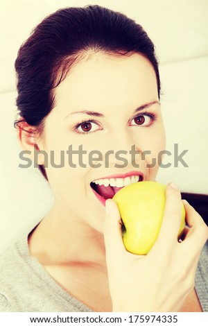 Portrait of a young beautiful and smiling woman taking a bite of a green apple.