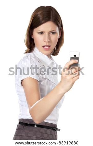 Portrait of a young beautiful angry businesswoman holding phone in her hand - stock photo