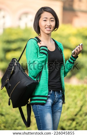 Portrait of a young beautiful asian student with university building in the background. - stock photo