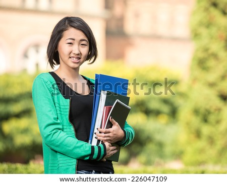 Portrait of a young beautiful asian student with university building in the background.