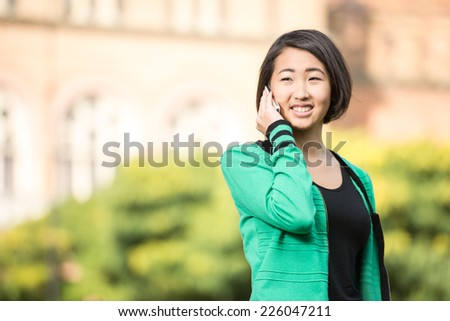Portrait of a young beautiful asian student with university building in the background. She is saying by phone. - stock photo
