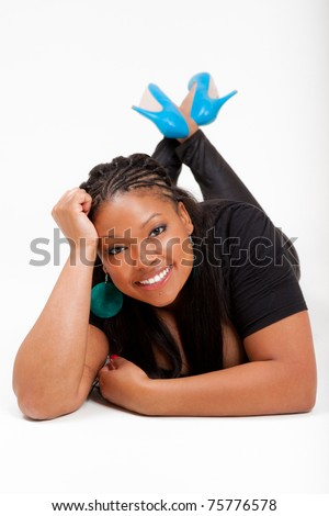 Portrait of a young beautiful black woman lied on the floor and smiling