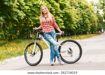 Portrait of a young beautiful blond girl with long hair posing near her mountain bicycle smiling wearing a red checkered shirt, in a green park full length - stock photo
