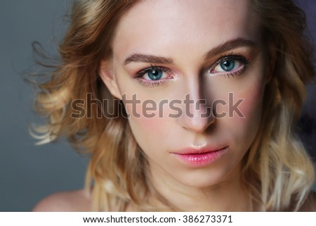 Portrait of a young beautiful blond woman with focus on the eyes