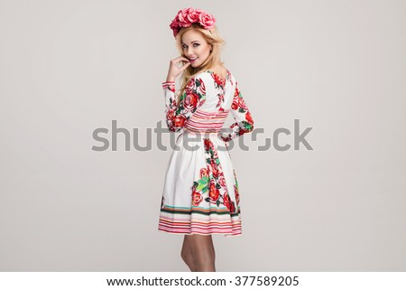 Portrait of a young beautiful blonde woman in floral dress with pink flowers on her head. Spring fashion photo - stock photo
