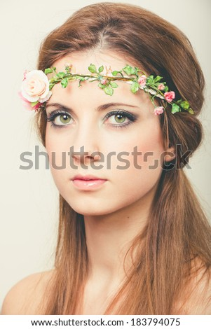 Portrait of a young beautiful blonde woman with long hair and green eyes with a tiara of artificial roses. - stock photo