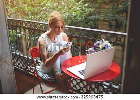 Portrait of a young beautiful blonde women chatting on her mobile phone while resting after work on laptop computer, charming female using cell telephone while sitting with net-book on a home terrace - stock photo