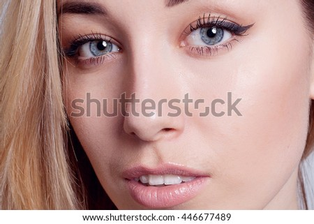 Portrait of a young beautiful blue-eyed girl. Beautiful make-up, perfectly smooth hair, blue eyes, open arms, perfect skin.