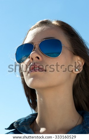 Portrait of a young beautiful brunette girl in sunglasses looking at the sky, close-up