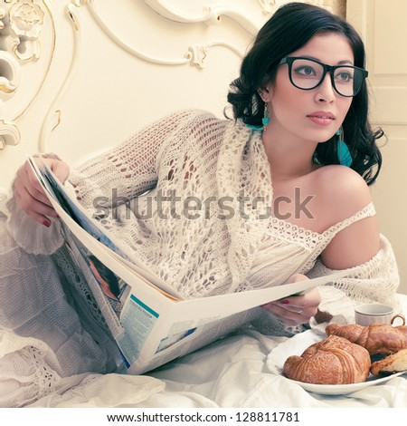 Portrait of a young beautiful brunette in a trendy glasses having breakfast (tea (coffee), croissants) and reading her morning newspaper in a vintage bedroom. Indoor shot - stock photo
