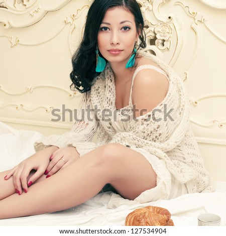 Portrait of a young beautiful brunette in a trendy having breakfast (tea (coffee), croissants) and posing on a bed in her vintage bedroom. Indoor shot