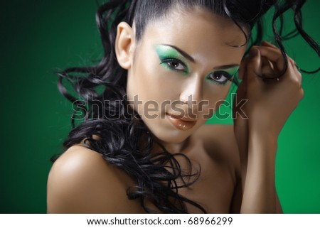 Portrait of a young beautiful brunette on a green background - stock photo
