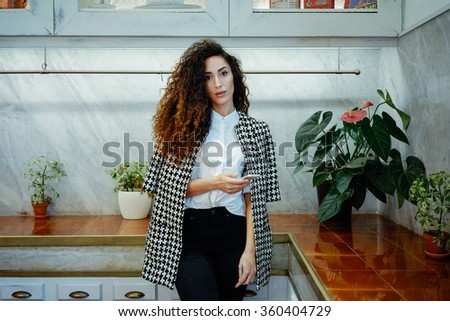 Portrait of a young beautiful business woman chatting on her phone in coffee-shop.Young charming female freelancer holding a mobile phone - stock photo