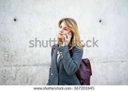 Portrait of a young beautiful business woman with blonde hair talking on the smart-phone while standing against gray concrete wall with copy space for your text o design - stock photo