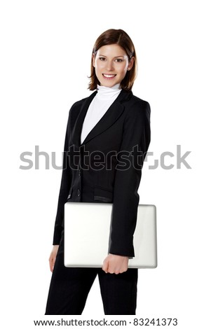 Portrait of a young beautiful businesswoman standing and holding laptop in her hand - stock photo
