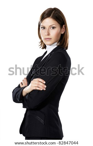 Portrait of a young beautiful businesswoman standing aside in black suit - stock photo