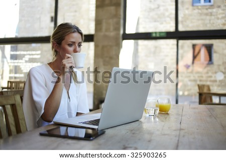 Portrait of a young beautiful businesswomen enjoying coffee during work on portable laptop computer, charming female student using net-book while sitting in cafe bar interior during morning breakfast - stock photo