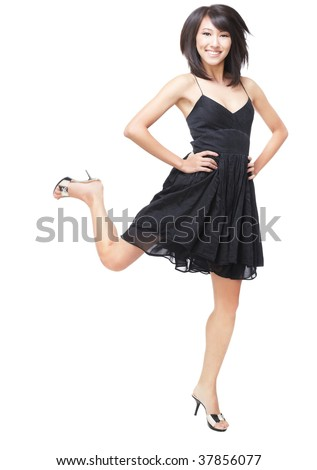 Portrait of a young, beautiful Chinese girl in black dress jumping with joy and excitement.  Focus on her eyes and face, motion blur with her feet to give a sense of movement - stock photo