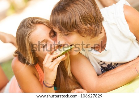 Portrait of a young beautiful couple eating melon