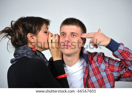 Portrait of a young beautiful couple woman is talking to the man's ear - stock photo