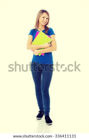 Portrait of a young beautiful female student with workbook. - stock photo