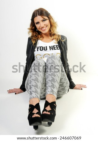 portrait of a Young beautiful funny smiling caucasian teen girl seating on the White background leaning backwards holding her legs in front of her chest - stock photo