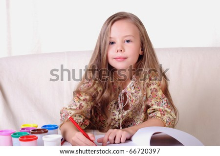 Portrait of a young beautiful girl. A girl is engaged in drawing