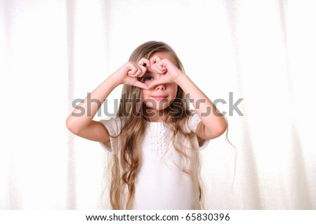 Portrait of a young beautiful girl. A girl makes a gesture in the form of the heart. - stock photo