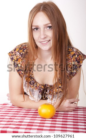 Portrait of a young beautiful girl holding orange and smiling.