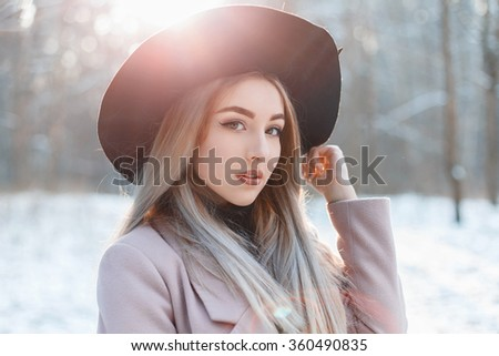 Portrait of a young beautiful girl in a black hat on a winter day at sunset