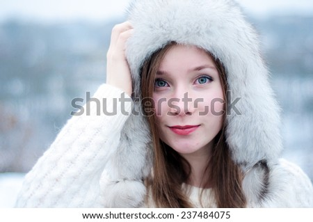 Portrait of a young beautiful girl in a cap with earflaps  in a cool winter park  - stock photo