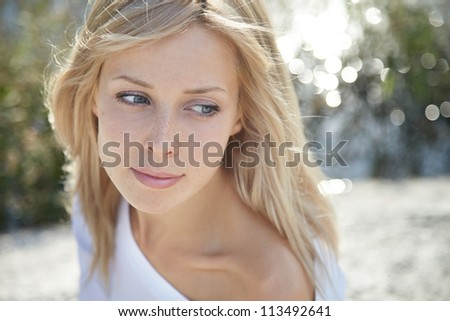 Portrait of a young beautiful girl relaxing on the shore of lake. - stock photo