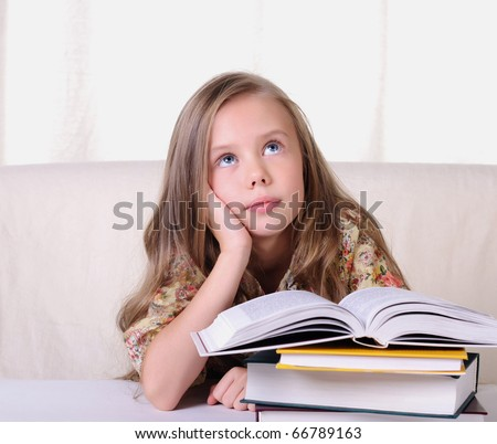 Portrait of a young beautiful girl. The girl is studying various textbooks. - stock photo