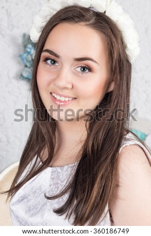 Portrait of a young beautiful girl with a wreath of white roses. Spring. Valentine's Day. Mothers Day.