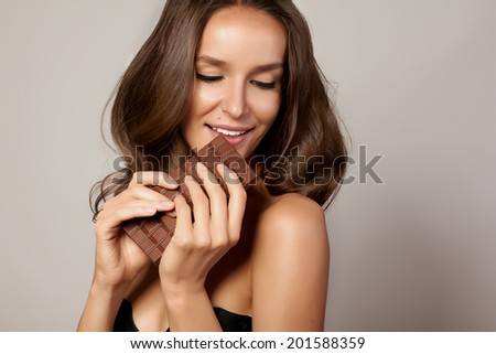Portrait of a young beautiful girl with dark curly hair, bare shoulders and neck, holding a chocolate bar to enjoy the taste and are dieting, healthy eating and organic foods, feeling temptation - stock photo
