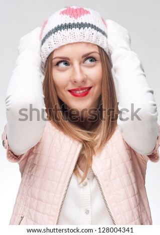 Portrait of a young beautiful girl with raised hands to the head and an intriguing look up and away - stock photo