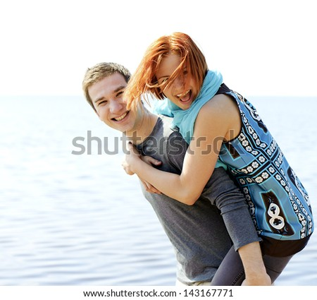 Portrait of a young beautiful happy couple outside man carrying woman smiling piggyback