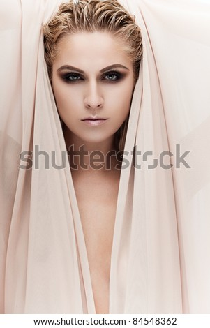 Portrait of a young beautiful lady covered with beige fabrics - stock photo